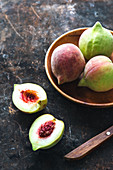 Green peaches in a wooden bowl and next to it