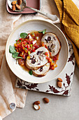 Turkey roulade with smoked ricotta, almonds and olives on cherry tomato salsa