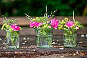 Ländliche Blumensträuße aus Rosen Frauenmantel und Wiesenblumen in Weckgläsern