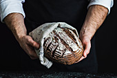 Man holding a spelt and wholewheat bread made with aronia (chokeberry) powder