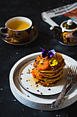 Oat pancakes with blood orange, honey, cocoa nibs and edible flowers served with cup of tea