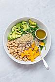 Quinoasalat mit Avocado, weissen Bohnen, Rucola, Spinat, Sonnenblumenkernen und Orange