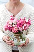 Frau hält Strauß aus Tulpen, Ranunkeln, Hyazinthen