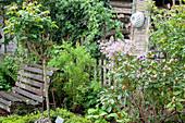 Gartenbank zwischen Gehölzen, alter Fensterladen mit Backform als Deko