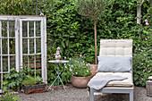 Ruheecke im Garten mit Sonnenliege, antikem Fenster und Dekoration
