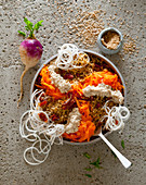 A bulgur bowl with radish, carrots, dried tomatoes and sesame seed cream cheese