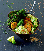Vegan kale bowl with guacamole, rice patties, cucumber and sesame seeds