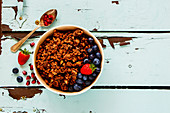 Chocolate granola bowl with fruit and berry