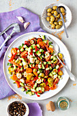 Veggies (tomatoes, pepper, cucumbers) salad with mozzarella and olives