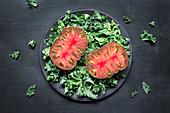 Tomatenscheiben auf Grünkohlblättern