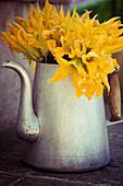 Courgette flowers in a metal jug