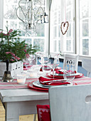 Table festively set in red and white in conservatory