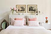 Doppelbett mit weißem Betthaupt als Ablage und pastellfarbener Bettwäsche