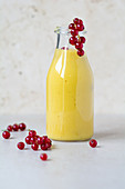 A mango smoothie with redcurrants