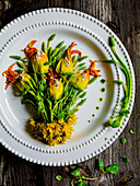 An arrangement of courgette flowers and wild asparagus on a plate