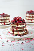 A stack of pancakes with cream and cherries