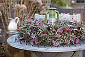 Herbstlicher Kranz mit Hagebutten liegt auf dem Tisch