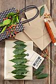 Geschenkverpackungen mit Lorbeerblättern und Hagebutten dekorieren
