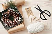 Zutaten für winterliche Geschenkverpackung, Kranz aus Zapfen