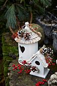 Vogelhäuschen winterlich dekoriert mit Zapfen, Winterbeere und Hagebutten