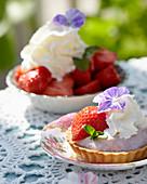 Erdbeer-Tartelette und Schale mit Erdbeeren, Schlagsahne und Hornveilchen-Blüte