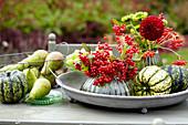 Herbststrauß mit Dahlien und Schneeballbeeren, Birnen und Kürbisse als Deko