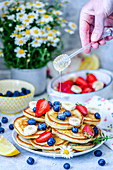 Pancakes with summer berries - blueberries, strawberries and banana and honey