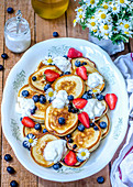 Pancakes with yogurt, honey, strawberries and blueberries