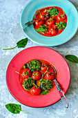 Spinach and ricotta cutlets with parmesan and garlic in tomato sauce with whole cherry tomatoes in red and blue plates