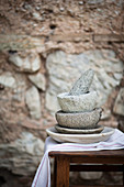 A stack of stone mortars with a pestle in front of a stone wall