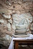 Gestapelte Steinmörser mit Stössel vor Steinmauer
