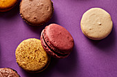 Assortment of colorful macarons on purple background