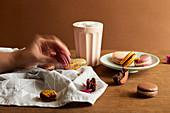Hand greift nach Macaron, bunte Macarons und Kaffeebecher auf Tisch