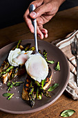 Putting poached egg on grilled asparagus and toasted bread