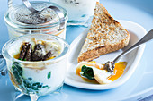 Eggs in a jar with morels and spinach leaves
