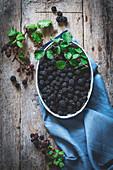 Ripe blackberries garnished by leaves in bowl
