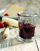 A jar of raspberry chutney with cheese