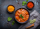Chicken tikka masala with spicy curry meat served in rustic ceramic bowl, popular Indian dish