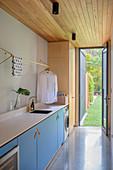 Hellblaue Schrankzeile mit integrieter Waschschmaschine, Waschbecken und Kleiderstangen