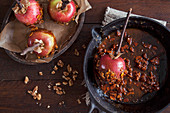 Making toffee apples with ripe red apples, dipping in toffee