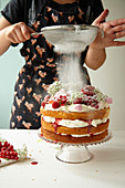 Victoria Sponge being dusted with icing sugar