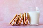 Sandwich Cookies mit Orangencreme und Himbeerpulver dazu ein Glas Milch