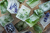 Homemade ice cubes with herbs, flowers and fruits