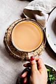 Frauenhand hält Tasse mit Chai-Tee
