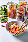 Fermentierter Kohl, Radieschen und Fisch in Gläsern und Schälchen (Korea)