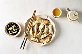 Fried asian dumplings Gyozas potstickers in white ceramic plate, bowl of soy onion sauce and teapot