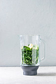 Ingredients for green spinach kale apple smoothie in glass blender on white marble table