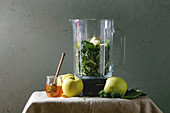 Ingredients for green spinach kale apple honey smoothie in glass blender and ingredients