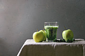 Green spinach kale apple smoothie in glass on linen table cloth with ingredients above