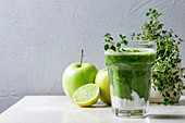 Green spinach kale apple honey smoothie in glass on white marble table with blender and ingredients above